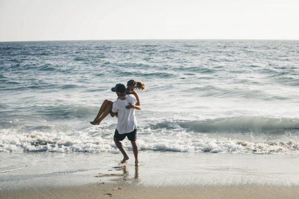 man holding woman on the beach