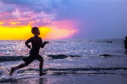 boy running to the ocean