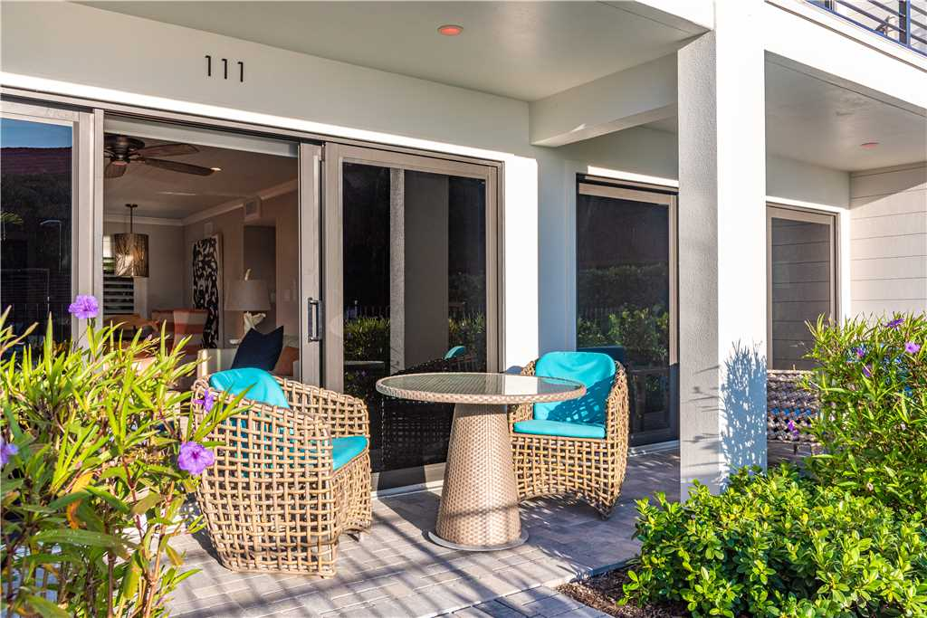 Exterior of patio with 2 wicker chairs and landscaping in Anna Maria Island