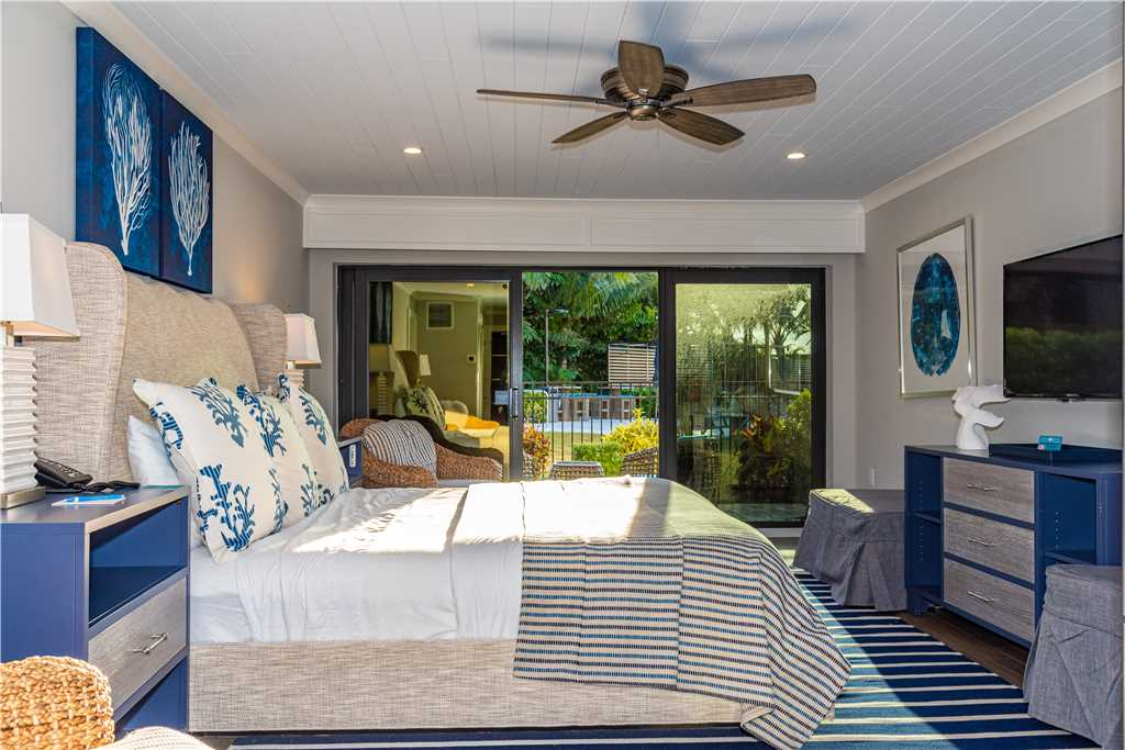 Interior of bedroom with queen bed and sliding glass door leading to patio in Anna Maria Island