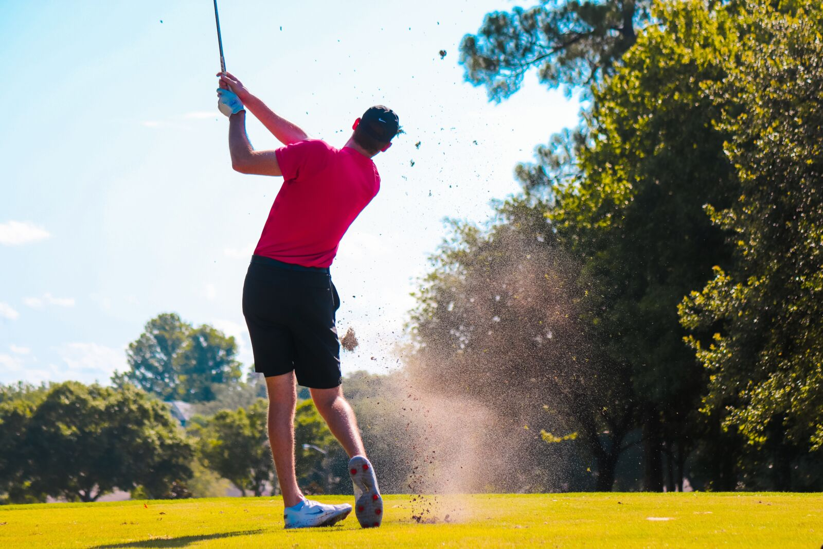 Man post hitting the golf ball