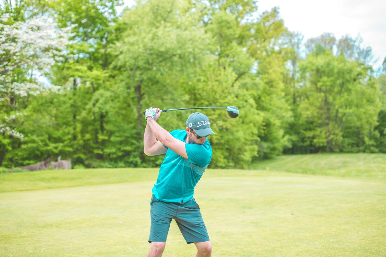 Man swinging to hit golf ball