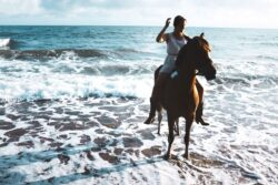 girl riding horse in ocean