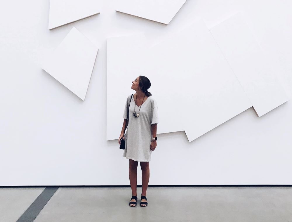 woman by a white wall in museum