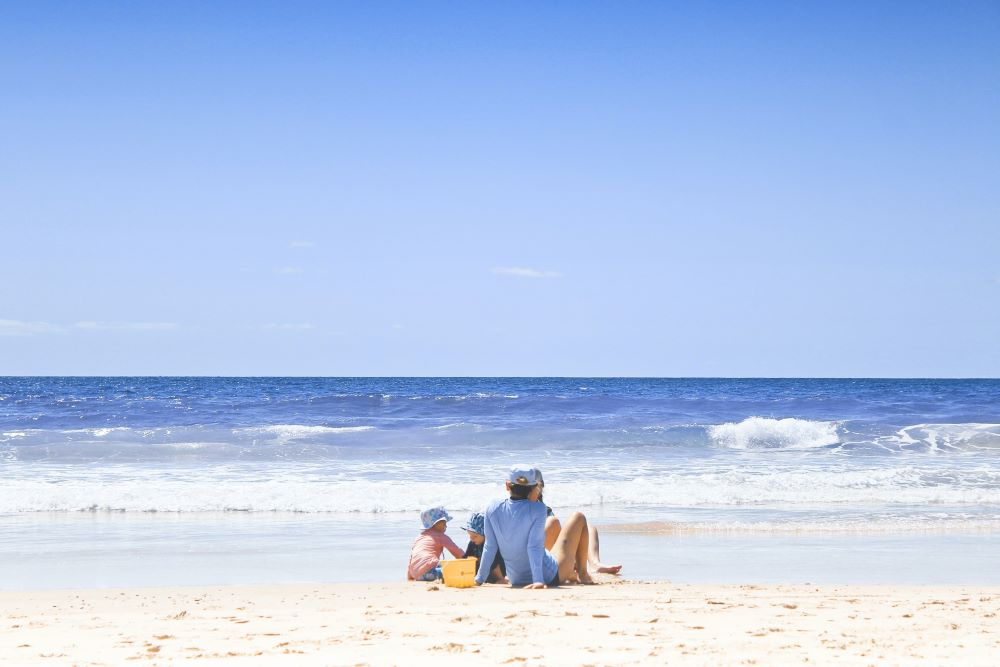 family sitting on beach together